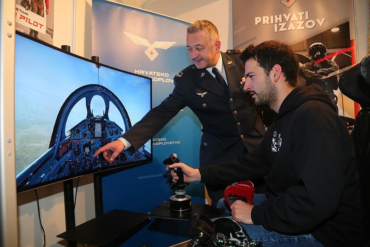 Zainteresirani posjetitelji imaju priliku na MORH-ovom promidžbenom štandu isprobati izložen kompjuterski simulator letenja borbenog aviona | Foto: MORH / D. Volarić